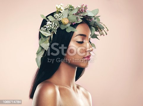 Studio shot of a beautiful young woman wearing a wreath while posing with her eyes closed against a pink background