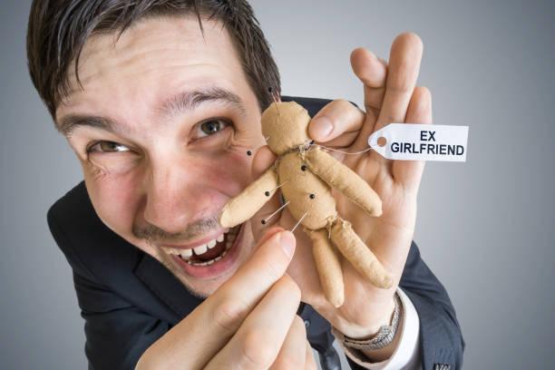 Notion de vengeance. Jeune homme et poupée vaudou avec étiquette ex-petite amie. - Photo