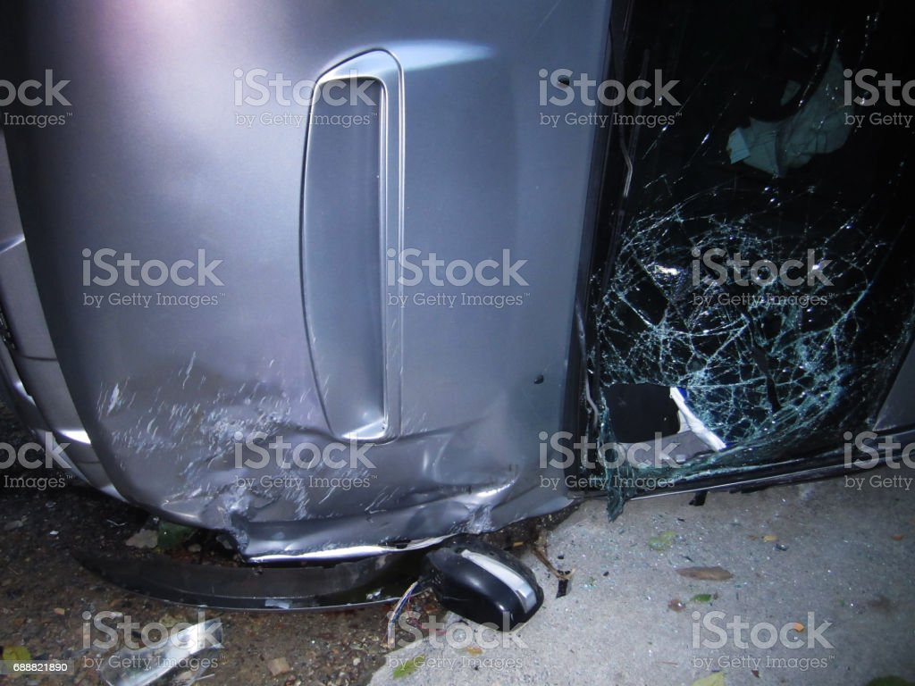 reversed car laying on the road after accident, shattered glass window of a car stock photo