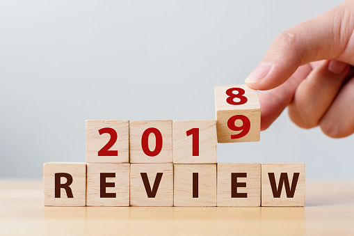 1163501702 istock photo 2019 review concept. Hand flip wood cube change year 2018 to 2019 and the word REVIEW on wooden block on wood table 1137969248
