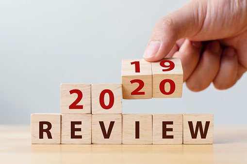 1163501702 istock photo 2020 review concept. Hand flip wood cube change year 2019 to 2020 and the word REVIEW on wooden block on wood table 1191588441