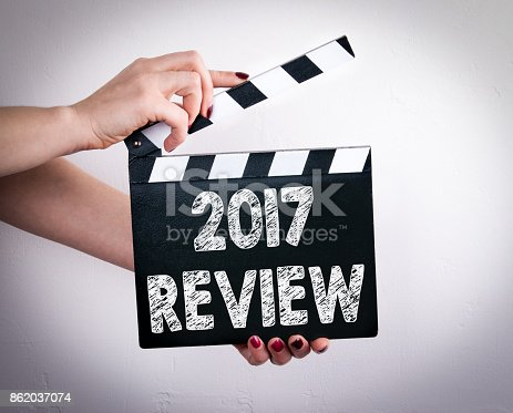 istock 2017 review. Female hands holding movie clapper 862037074