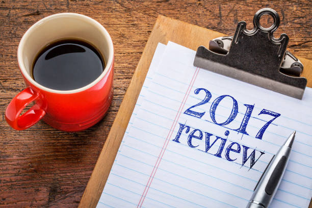 2017 review on blackboard on clipboard 2017 year review on clipboard and coffee against grunge wood desk 2017 stock pictures, royalty-free photos & images