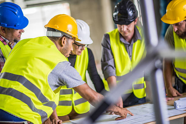 Reviewing blueprint Construction workers and architect wearing reflective clothing reviewing blueprint at construction site. reflective clothing stock pictures, royalty-free photos & images
