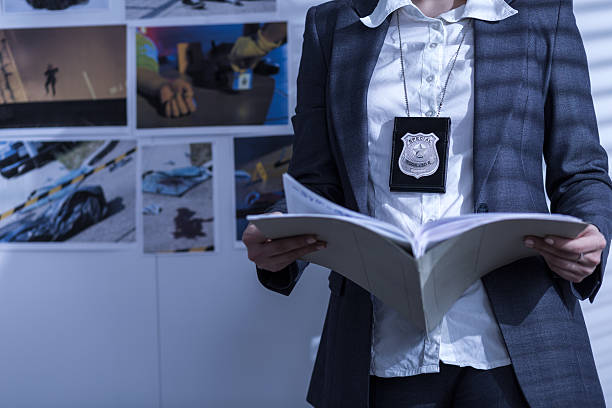 Reviewing files and documents Police woman is reviewing files and documents detective stock pictures, royalty-free photos & images