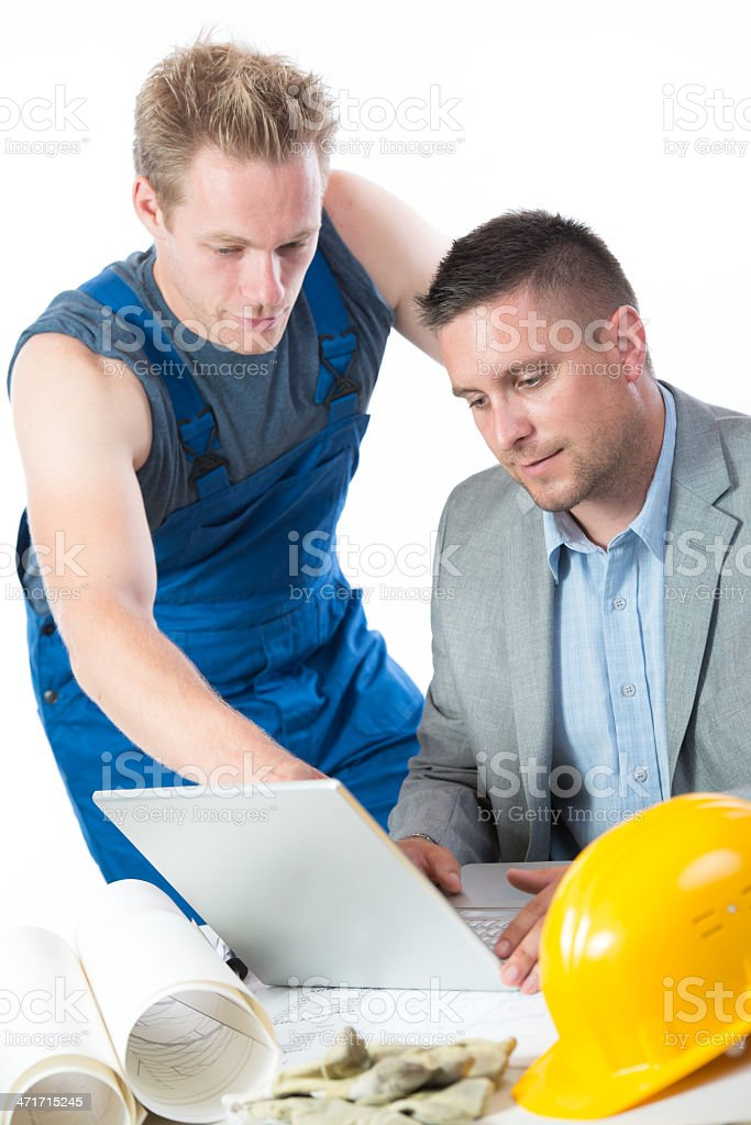 Reviewing plans on laptop royalty-free stock photo