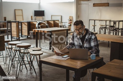 Carpenter in his showroom using laptop and working on project. Mature man in casual clothing.