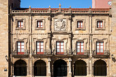 Gijon, Spain-August 31, 2018: Front view of Revillagigedo palace stone facade, Gijon, Asturias, Spain. Ancient monument XVIII century with coat of arms, windows, balconies,arcade, arches, clear blue sky.