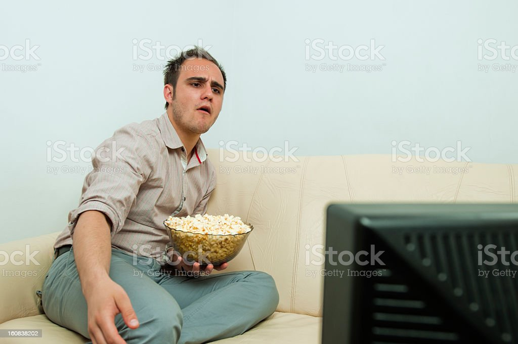 Revolted man, watching a game on TV, eating popcorn stock photo