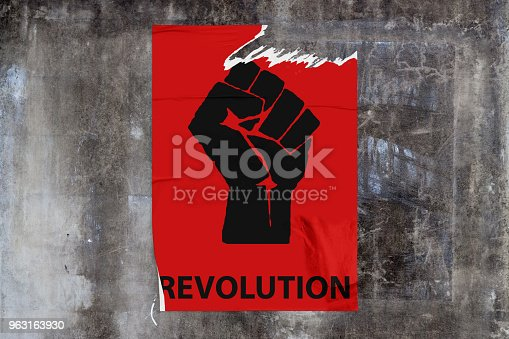 Full-frame weathered concrete wall with a torn red poster in the middle depicting a black fist with