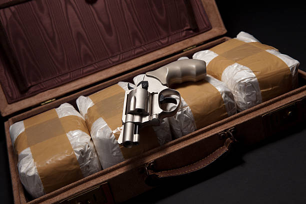 Revolver and Drugs in a Briefcase A revolver lies on top of bundles of powdered drugs in a briefcase. Studio shot. drug cartel stock pictures, royalty-free photos & images