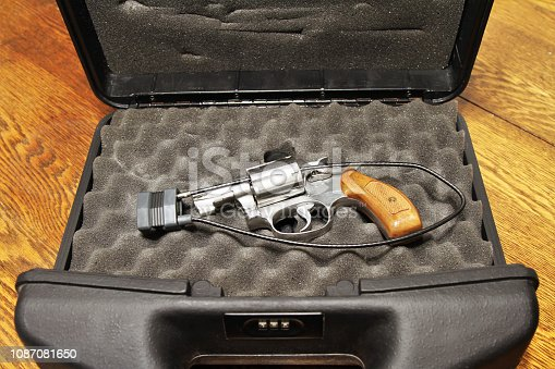 Revolver in lock case with combination lock for secure storage. Gun is also secured with a cable padlock through the open bullet cylinder.