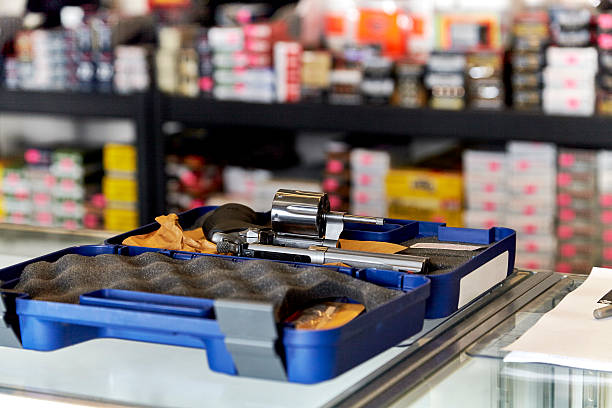 Revolver on Counter in Retail Store Revolver on on glass showcase displayed in case with rows of ammunition in the background gun shop stock pictures, royalty-free photos & images