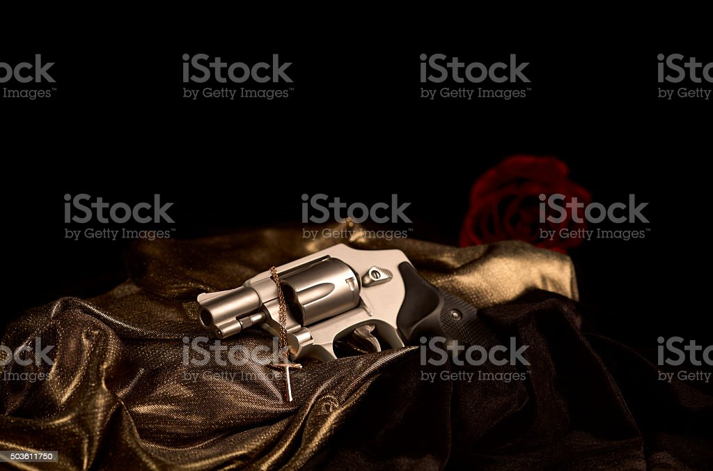 Revolver with a Cross Necklace stock photo