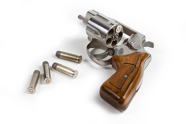 Revolver with bullets on white background stock photo