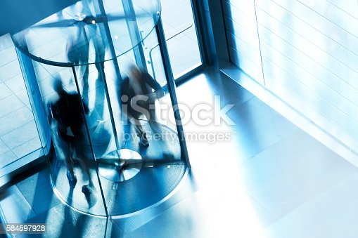 A high angle view of a people entering and exiting an office building through a revolving door. A slow shutter speed allows for the anonymity of the people as they quickly move through the rotating door.  A cool blue cast dominates the scene.
