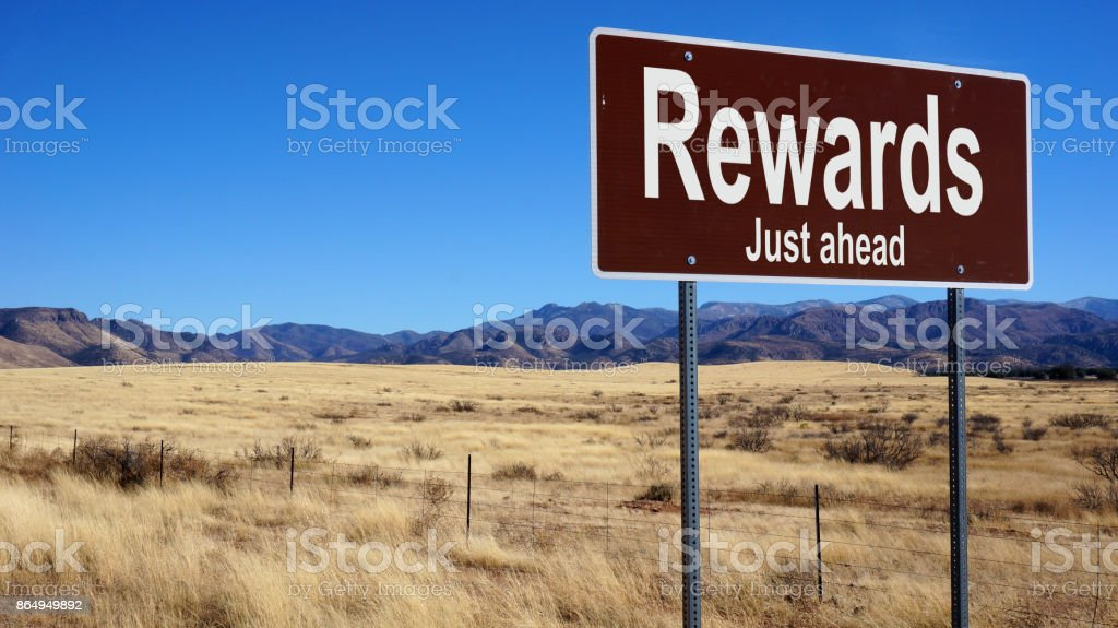 Rewards brown road sign стоковое фото