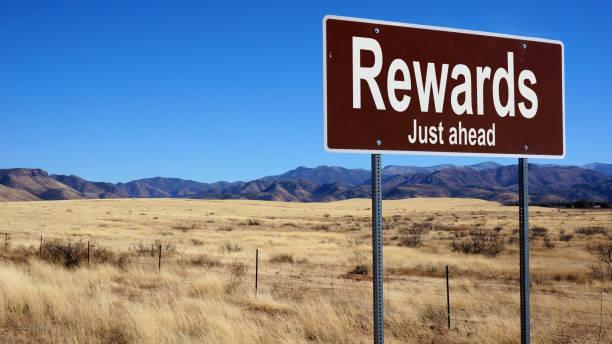 rewards brown road sign - incentivo foto e immagini stock