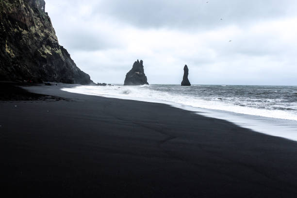 Reynisfjara is a world-famous black-sand beach on the South Coast of Iceland. Basalt rocks Reynisdrangar, black volcanic sand and Atlantic ocean on a gloomy day in Iceland. black sand stock pictures, royalty-free photos & images