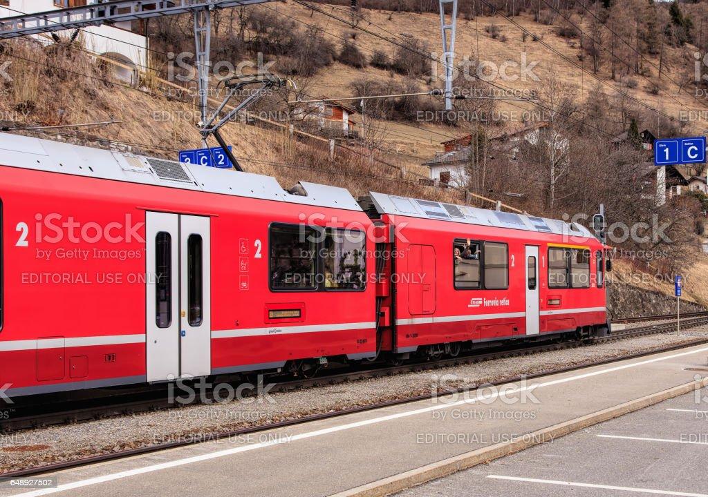Rhaetian Railway train leaving the Filisur railway station in Switzerland stock photo