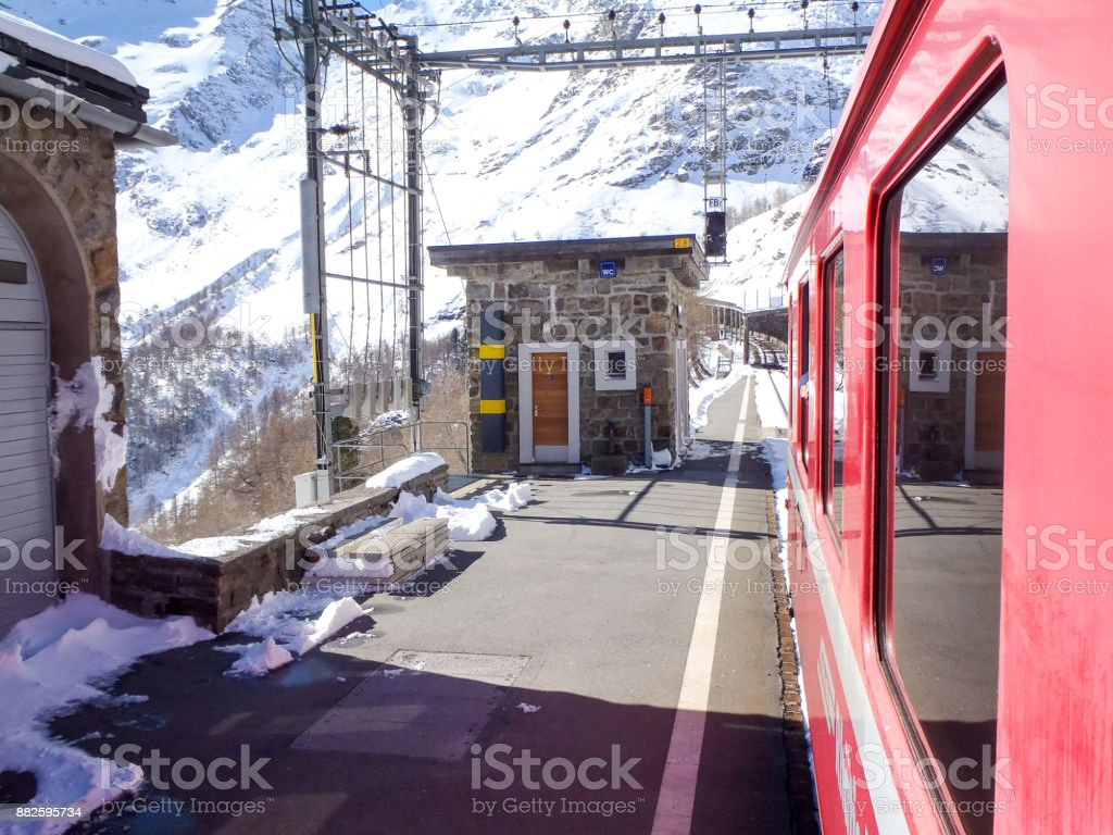 Rhaetian Railway train parked at the station stock photo