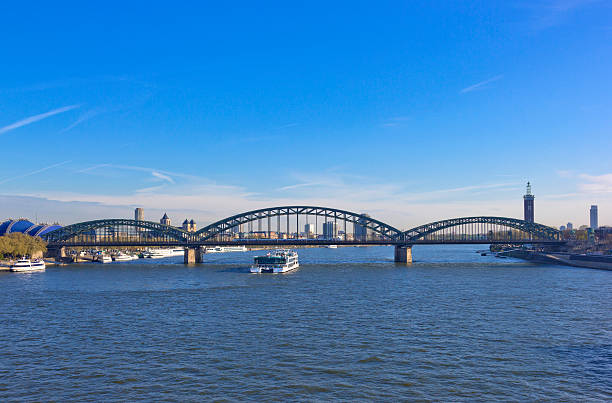 rhine landscape with hohenzollern bridge and ship in cologne, germany - hohenzollernbrücke stock-fotos und bilder