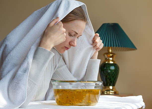 rhinitis treatment at home by inhalation young woman doing inhalation of the upper respiratory tract of health decoction of chamomile smoke inhalation stock pictures, royalty-free photos & images