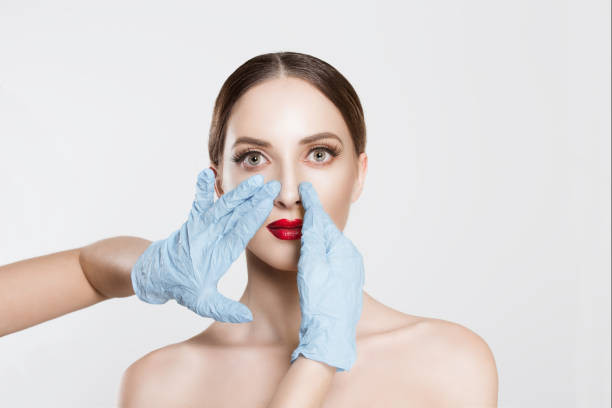 Rhinoplasty. wish to be beautiful need for beauty. Closeup portrait doctor hands with gloves  touching woman face nose want to change her form do plastic surgery.  cropped image horizontal studio shot stock photo