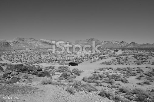 Rhyolite is a ghost town in Nye County, in the U.S. state of Nevada. It is in the Bullfrog Hills, about 120 miles (190 km) northwest of Las Vegas, near the eastern edge of Death Valley. The town began in early 1905 as one of several mining camps that sprang up after a prospecting discovery in the surrounding hills. During an ensuing gold rush, thousands of gold-seekers, developers, miners and service providers flocked to the Bullfrog Mining District. Many settled in Rhyolite, which lay in a sheltered desert basin near the region's biggest producer, the Montgomery Shoshone Mine.