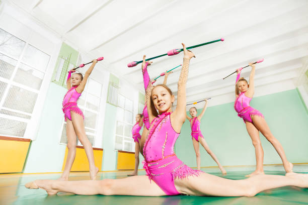 rhythmic gymnast performing exercise with clubs - leotard stock photos and pictures