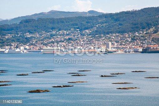 Ria de Pontevedra view, bateas used to grow mussels, and Marín village townscape in the background  in Rias Baixas,  Ria de Pontevedra, Galicia, Spain.