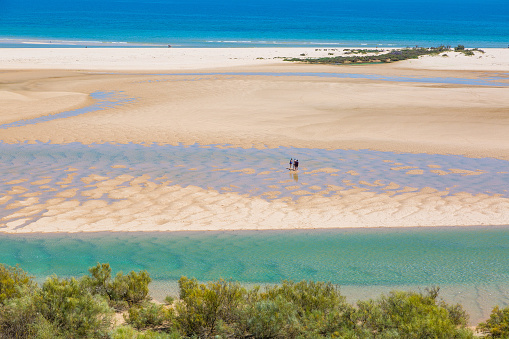 Lowtide aerial view of tourists walking across a sand bar at the Ria Formosa in Portugal.