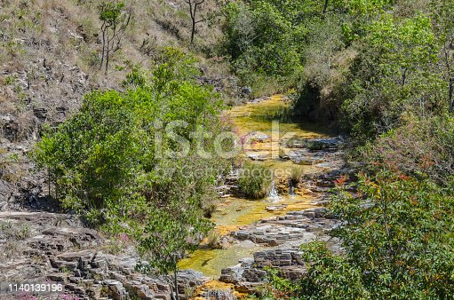 Small clean spring in a canyon opening. The river bed is carved on rock and therefore the mineral water running remains clean all the way down to the big Furnas lake.  A small spring is called