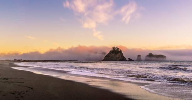Rialto Beach in der Dämmerung mit Meeresstapeln bedeckt mit Wolken aus dem Ozean, Olympic National Park, Washington State, USA. – Foto