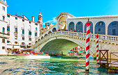 The Rialto Bridge in Venice on sunny summer day, Italy. Boat and people on the bridge a bit in motion blur!