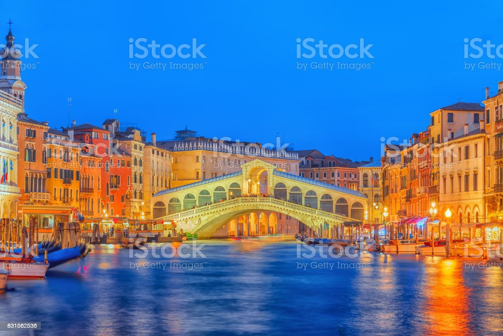 Rialto Bridge (Ponte di Rialto) or Bridge of Sighs and view of the most beautiful canal of Venice - Grand Canal and boats, gondolas, mansions along. Night view. stock photo