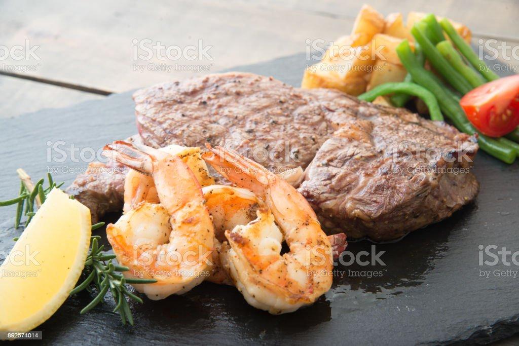 rib eye steak and grilled shrimp on black plate stock photo