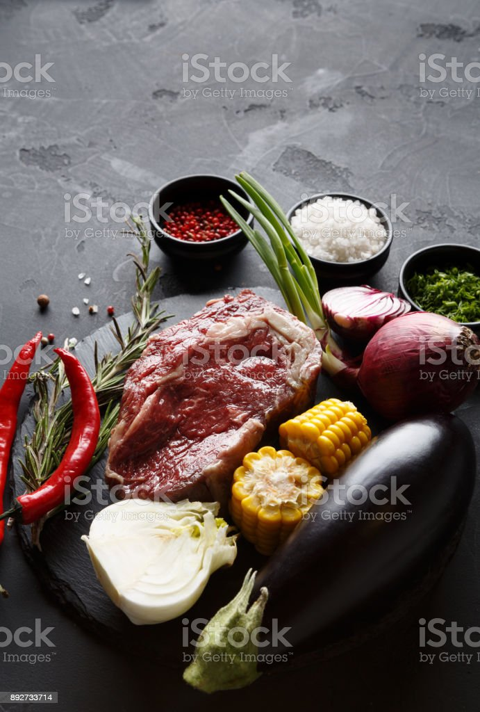 Rib eye steak and vegetables on plate at black background stock photo