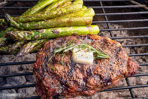 Rib Eye Steak with Asparagus on a Hot Charcoal Grill with butter, herbs and Flames
