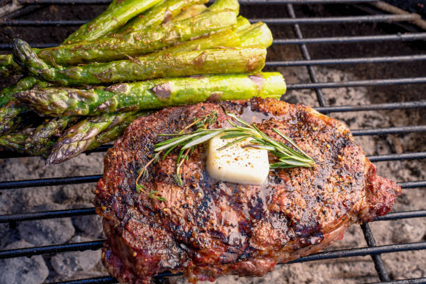 Rib Eye Steak with Asparagus on a Hot Charcoal Grill with butter, herbs and Flames stock photo