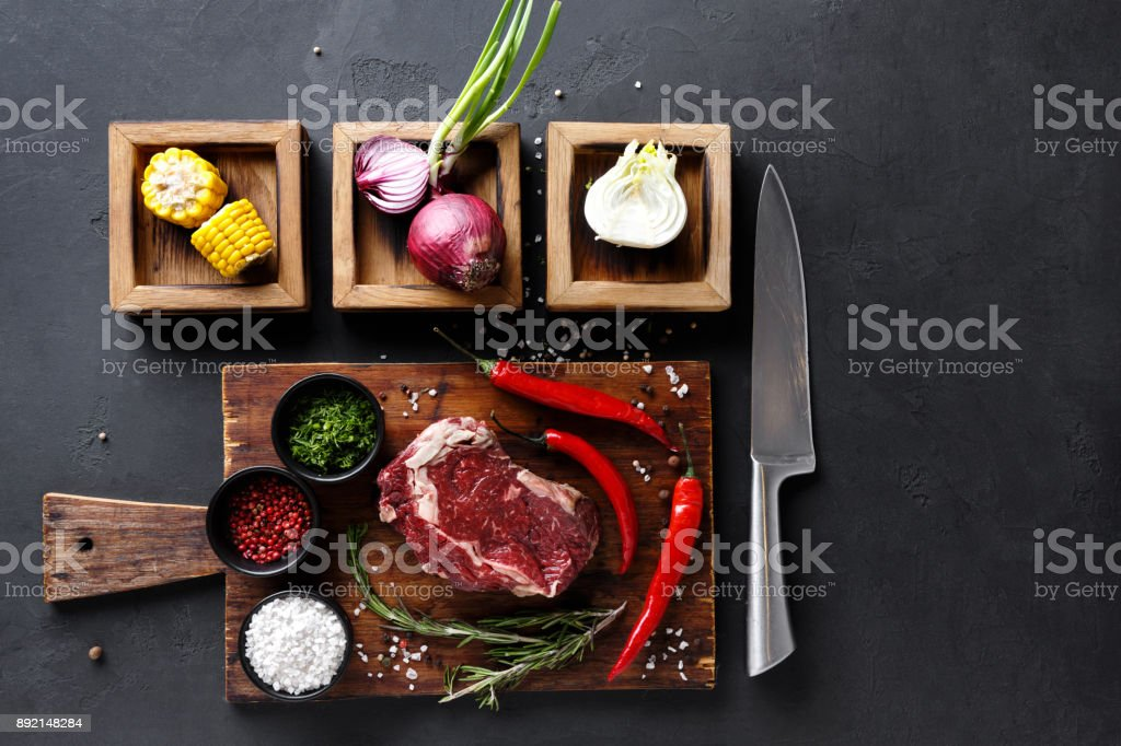 Rib eye steak with spices on wooden desk and diverse cooking ingredients in wooden boxes. stock photo