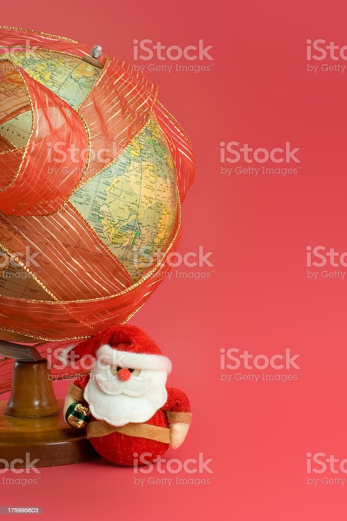 """Ribbon wrapped Globe with Santa Claus """"Santa Claus, right next to the world globe, wrapped in a festive red ribbon. Lots of copy-space provided."""" 2007 Stock Photo"""