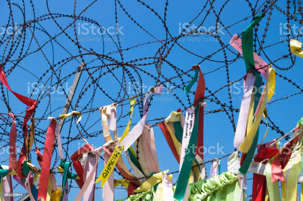 Ribbons tied at barbed wire at a fence at the demilitarised zone DMZ at the freedom bridge, South Korea, Asia stock photo