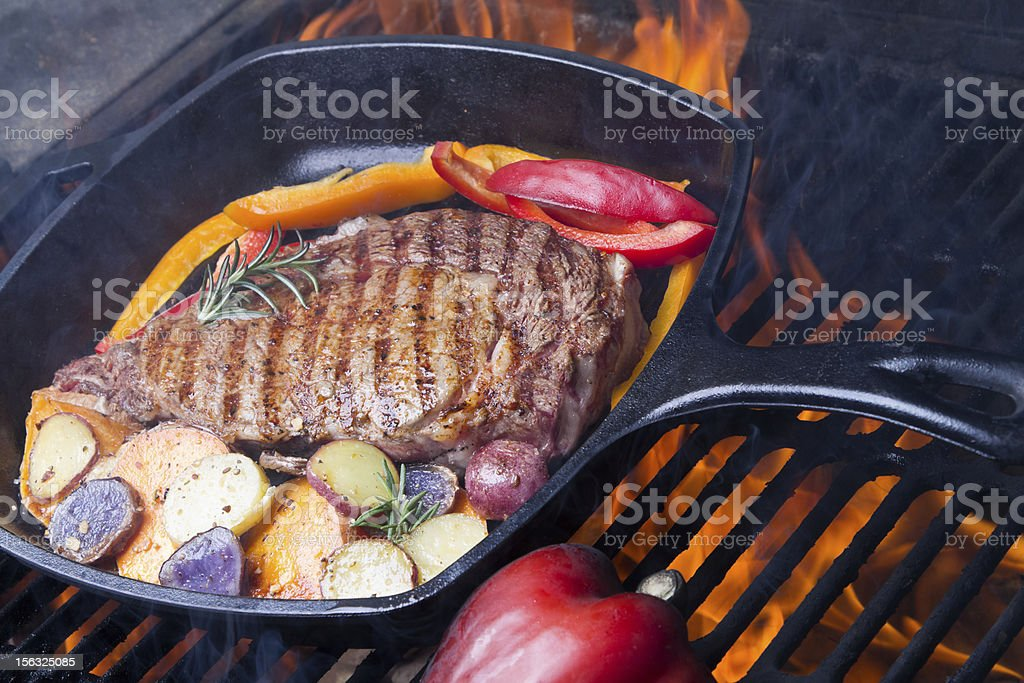 Ribeye Steak Roasted Potatoes and Peppers on Grill royalty-free stock photo