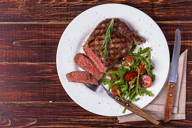 ribeye steak with arugula and tomatoes. - sirloin stockfoto's en -beelden