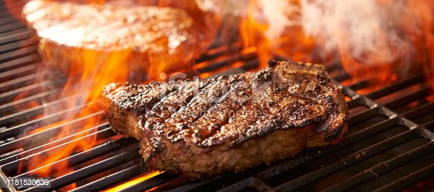 rib-eye steaks cooking on flaming grill panorama close up