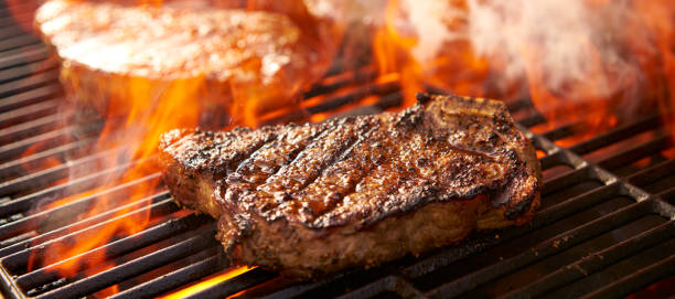 rib-eye steaks koken op flaming grill panorama - strip steak stockfoto's en -beelden