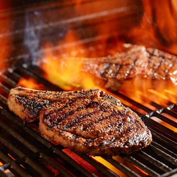 ribeye steaks on the grill over the open flame - ribeye biefstuk stockfoto's en -beelden