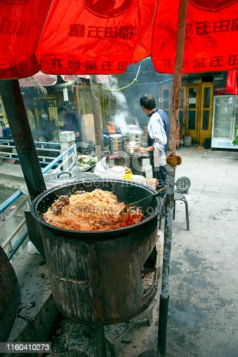 Tashgurkan, China - September 7th, 2018 : Rice and lamb meat kooking on a coal stove, steamy buns being prepared in the background.