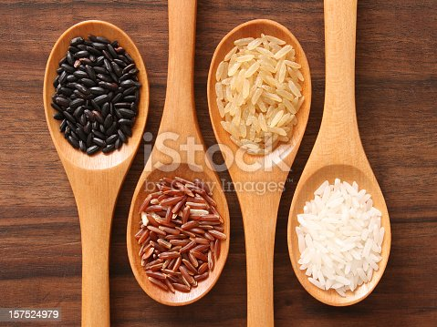 Four spoons with varieties of rice (black,red,brown,white)